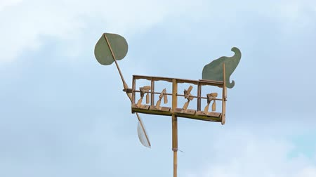 holiday makers : Improvised weathervane stands against a partly cloudy sky with a wind powered propeller which activates bamboo chimes. Stock Footage