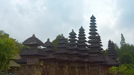 tiered : Long orderly row of structures with tiered thatched roofs at Pura Taman Ayun the royal Hindu temple complex in Bali, Indonesia.