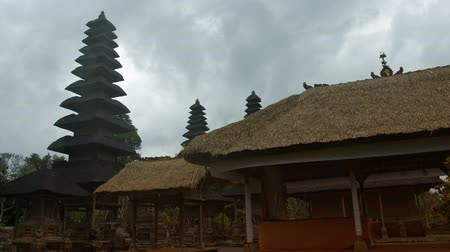 tiered : Unique architecture of Pura Taman Ayun Temple with tiered pagoda roofs set against a gray overcast sky in Bali, Indonesia. Stock Footage