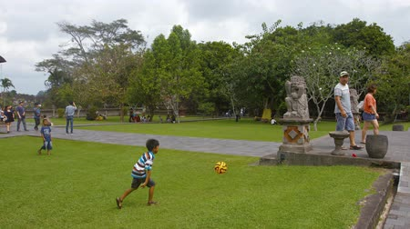 délkelet Ázsia : BALI. INDONESIA - CIRCA JUL 2015: Childen playing football in the grass outside the main complex of Taman Ayun Temple in Bali. Indonesia. Video 4k UHD Stock mozgókép