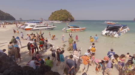 speedboats : TUP ISLAND. THAILAND - CIRCA FEB 2015: Huge crowd of tourists on the tropical. sandy beach of Tup Island in Thailand. FullHD video