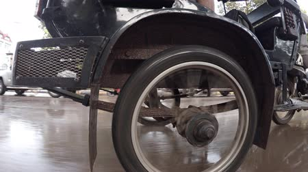 improvised : Wheel of motorcycle rickshaw close up. Movement on a rainy day. UltraHD 4k footage