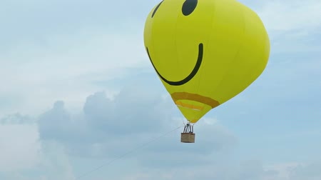 авиашоу : KIEV. UKRAINE - 29 MAY 2016: Bright yellow hot air balloon. with a smiley face. tethered at Chaika Air Fest as aircraft zoom by. Footage 1920x1080