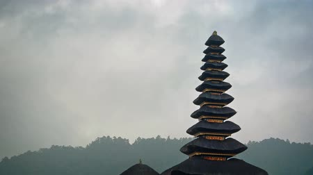 bratan : Rain clouds slowly drift over the exotic. tiered pagodas of Pura ulun Danu Bratan. a Hindu temple in Bali. Indonesia.