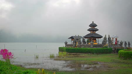 bratan : Misty rain obscures the far bank of the lake at Pura Ulun Danu Bratan. a Hindu temple in Bali. Indonesia.