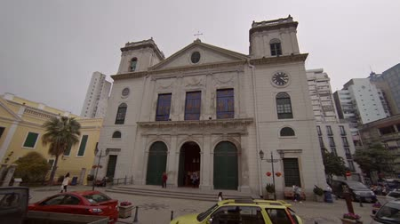 palce : MACAU. CHINA - CIRCA JAN 2015: Traffic inches along a narrow. winding road and past a historic church in Macau