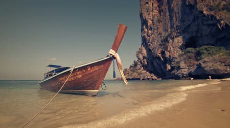 tradicional : AO NANG. KRABI. THAILAND - CIRCA FEB 2015: Wooden longtail boat. tied on a tropical beach paradise in Thailand. with huge rock formations