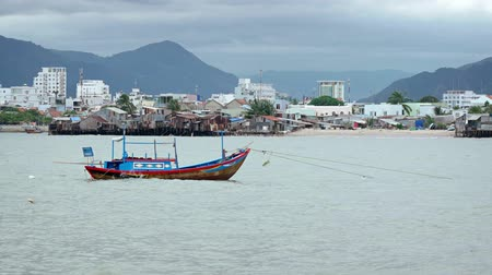 improvised : Wooden fishing boat. painted in blue and red. at anchor off an impoverished community of improvised housing near Nha Trang. Vietnam. Stock Footage