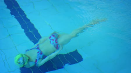 кусок : Female swimmer crosses the frame. swimming underwater with cap and goggles in a public swimming pool. FullHD footage Стоковые видеозаписи