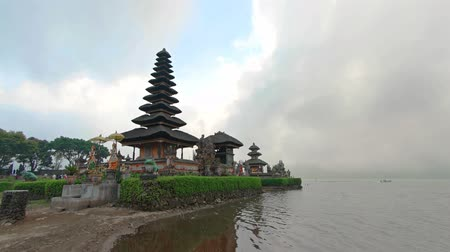 bratan : Tourists visit the beautiful. Pura Ulun Danu Bratan. a lakeside. Hindu temple with tiered pagodas and landscaped gardens in Bali Indonsia. Stock Footage