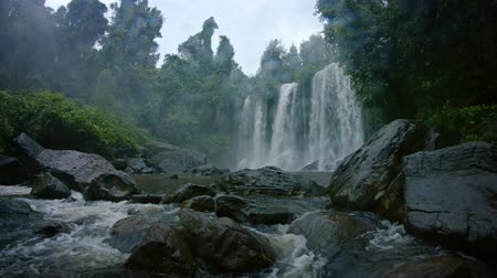 řev : River Water Tumbling over a Natural Waterfall and amongst Boulders in a Cambodian wilderness. with sound. UHD 4k