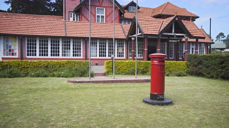 postacı : NUWARA ELIYA. SRI LANKA - CIRCA DEC 2016: Public Post Box Standing in front of Old Post Office Building
