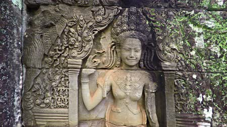 божество : 4k video - The woman carved on a stone wall of an ancient temple. Cambodia. Bayon temple Стоковые видеозаписи