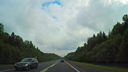 flanked : Passenger perspective of a road trip along a busy. rural. two lane highway. in Russia. flanked by forest on either side. FullHD video Stock Footage