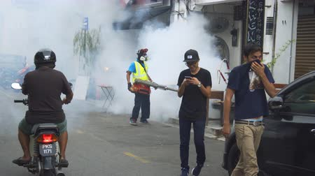 komary : GEORGE TOWN. PENANG. MALAYSIA - CIRCA MAY 2017: Local man fumigating along a city street to stop mosquitos and the spread of Dengue Fever. UltraHD 4k video