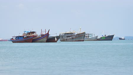 georgetown : Row of fishing vessels in varying sizes. anchored near the beach off Georgetown. Penang. Malaysia. under sunny skies. UltraHD 4k video