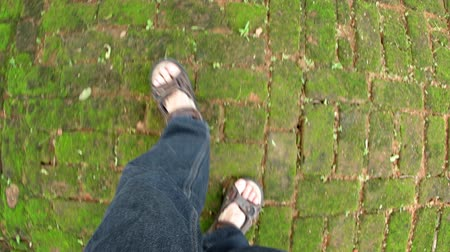 polonnaruwa : Denim clad legs and sandaled feet walking over irregular. mossy pavers at a park in Polonnaruwa. Sri Lanka. FullHD 1080p video