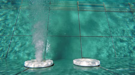 ar : Submerged perspective of a nozzle spewing water and bubbles through an outlet in the blue. tiled wall of a swimming pool. UltraHD 4k footage Stock Footage