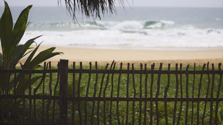 separação : Simple fence separates a private bungalow compound from the tropical beach with rolling breakers. just a few steps away. UltraHD 4k video