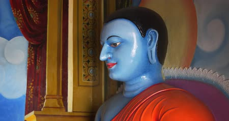 earlobe : Sculpted and blue painted image of the Buddha in a seated position. inside a Buddhist temple in Sri Lanka. 4k DCI footage