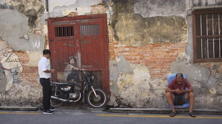 georgetown : GEORGE TOWN. PENANG. MALAYSIA - CIRCA MAY 2017: Tourists and the famous wall paintings (Boy on a motorcycle). Video Ultra HD 4k