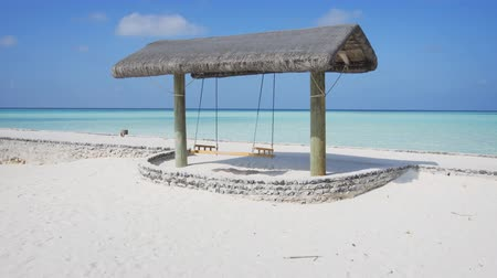 suspensão : Romantic bench swing sways beneath the shade of a nipa shelter. facing the clear water of the tropical ocean in the Maldives.