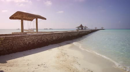 abrigo : Bench swing sways peacefully over a rocky pier as gentle waves wash over white sand. at this tropical beach in the Maldives.