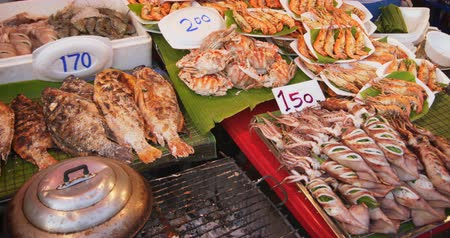 kalamar : Variety of grilled seafoods. including squid. tilapia. crabs and prawns. displayed for sale at an outdoor public market in Asia. DCI 4k video Stok Video