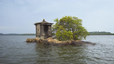 hikkaduwa : Tiny island with a religious shrine and sparse growth of young mangrove trees. in a river delta near Hikkaduwa. Sri Lanka. Ultra HD 4k video