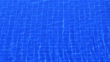 convidar : Surface of a pool with ripples and waves from a gentle breeze. distorting the grid of blue tiles on the bottom. Ultra HD 4k video