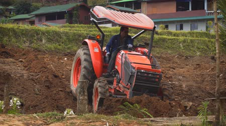 wheel loader : CHIANG MAI. THAILAND - JAN 2018: Local farmer uses a tractor to level the soil on a rural plantation.