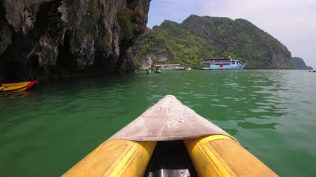 бортовой : Kayaking through peaceful green sea waters. beneath overhanging limestone cliffs. from an onboard perspective. in Phang Nga Province. Thailand. Стоковые видеозаписи