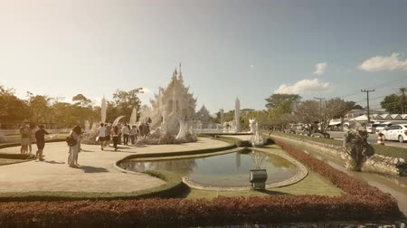 посещающий : CHIANG RAI. THAILAND - JAN 2018: Visitors approaching the ornate facade of Wat Rong Khun. the White Temple