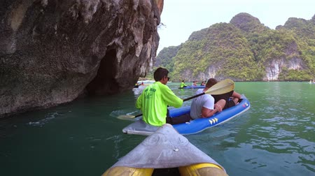 бортовой : PHANG-NGA. THAILAND - APR 2018: Onboard perspective of a kayaking tour beneath enormous. limestone sea cliffs in Thailand.