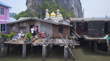 fishing village : Gold-domed mosque and dramatic limstone formation presiding over these houses on stilts at the remote Panyee Island. in Thailand. Ultra HD stock footage Stock Footage