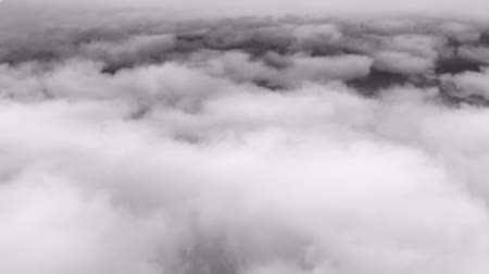 szürkeárnyalatos : Layer of dense. fluffy clouds clouds in grayscale. drifting slowly below. from an aerial perspective. 4k footage