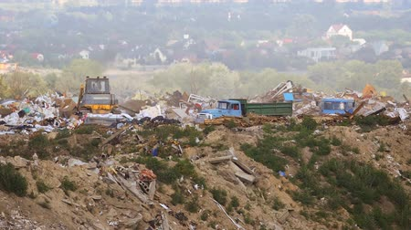 mal cheiroso : Bulldozer pushes piles of waste as dump trucks unload garbage at a municipal landfill. Video FullHD