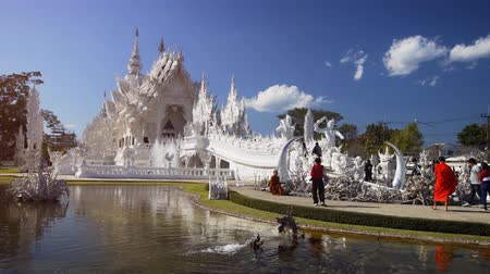spraying : CHIANG RAI. THAILAND - JAN 2018: Monk in Orange Robes takes Photos of White Temple with Smarphone. Stock footage 4k