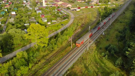 пригородный : LUKINO. NIZHNY NOVGOROD OBLAST. RUSSIA - AUG 2018: Aerial View of a Commuter Train Passing through Lukino. 4k UltraHD footage Стоковые видеозаписи