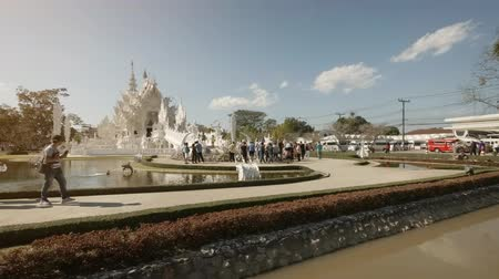 spletitý : CHIANG RAI. THAILAND - JAN 2018: Visitors approaching the facade of Wat Rong Khun. the White Temple. 4k stock footage Dostupné videozáznamy