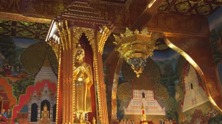murals : CHIANG MAI. THAILAND JAN 2018: Golden Buddha Statue and Ornate Interior of Wat Phra Singh Woramahawihan Temple. Video UltraHD 4k