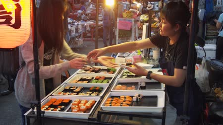 vendiendo : CHIANG MAI. Tailandia enero 2018: Vndor local vendiendo sushi en el mercado nocturno en Chiang Mai. Video UltraHD 4k Archivo de Video