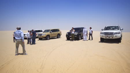 truck stop : STATE OF QATAR - MAY 2018: Tourists on Safari Stop in the hot Desert Stock Footage