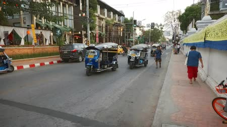 rickshaw : CHIANG MAI. THAILAND JAN 2018: Typical Tour Bus and Tuk Tuk Traffic on Chiang Mai Street. FullHD stock video Stock Footage