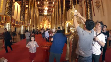 yaldız : CHIANG MAI. THAILAND JAN 2018: Worshippers Applying Gold Leaf to Buddha Statue as an Offering. Video UltraHD 4k Stok Video