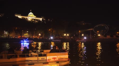 TBILISI. GEORGIA - OCT 07. 2018: Boats Cruise the Mtkvari River at night. with the Georgian Presidential Palace in the Background