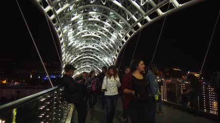 TBILISI. GEORGIA - OCT 07. 2018: People Strolling across the Bridge of Peace. with its thousands of illuminated LEDs. over the Mtkvari River. Стоковые видеозаписи