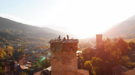 MESTIA. GEORGIA - OCT 2018: Tourists. standing atop a svan tower in the rural town of Mestia Georgia. silhouetted against the setting sun. Video 4k