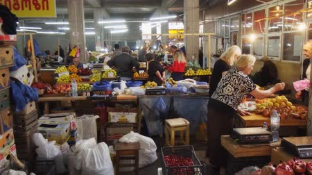 KUTAISI. GEORGIA - OCT 2018: Vendors sell fresh fruit at the indoor. public market in Kutaisi. Стоковые видеозаписи
