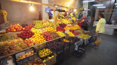 KUTAISI. GEORGIA - OCT 2018: Local shoppers buying fresh fruit at a vendor stall at Kutaisi Public Market.